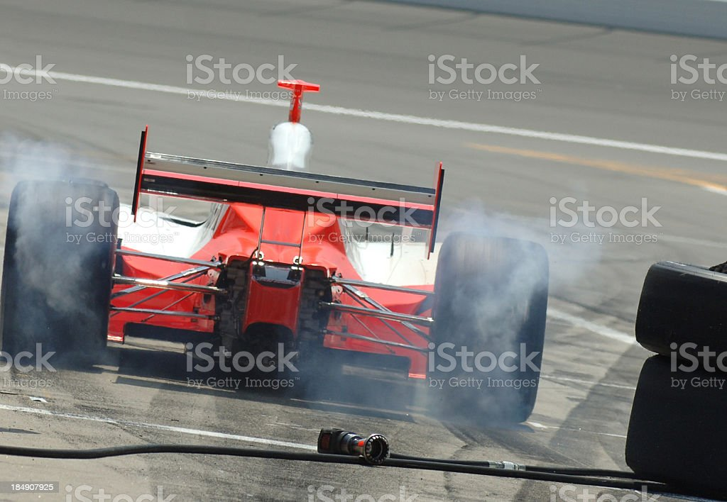 Racecar driver coming to a pit stop for crew to fix the car stock photo