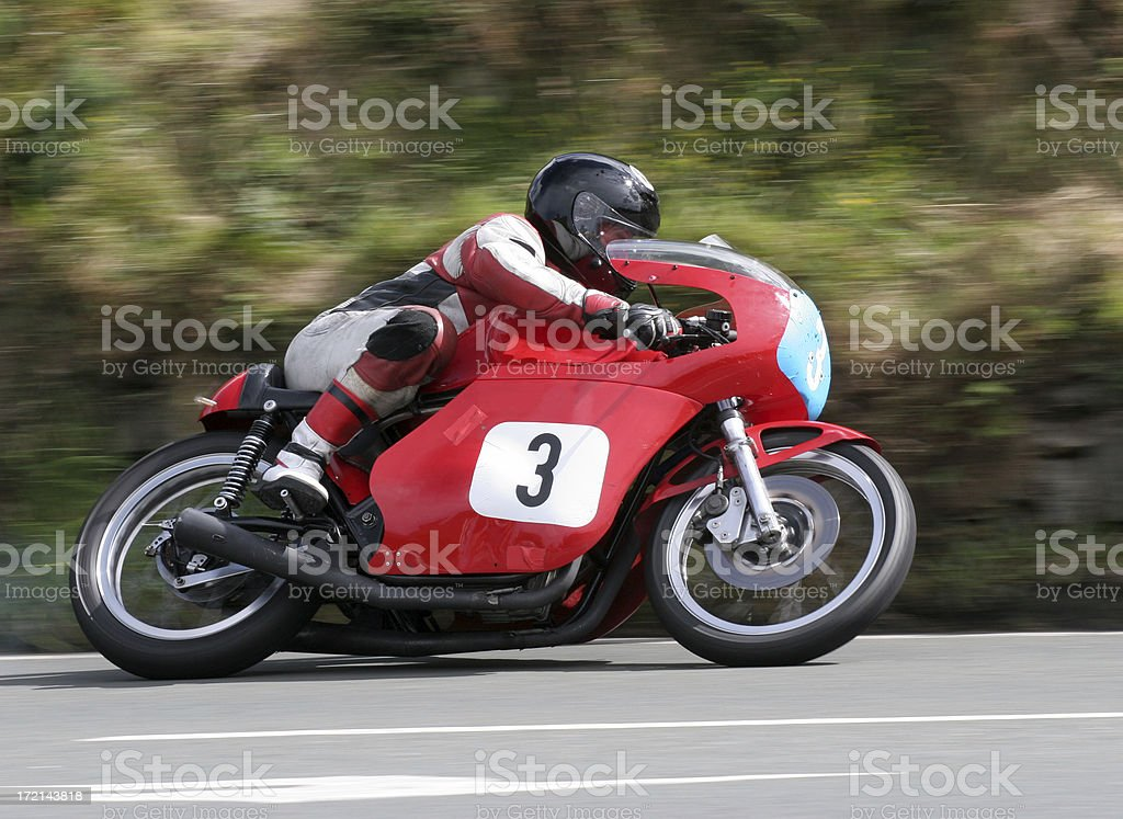 A racer on a red motorcycle with matching gear on the road stock photo