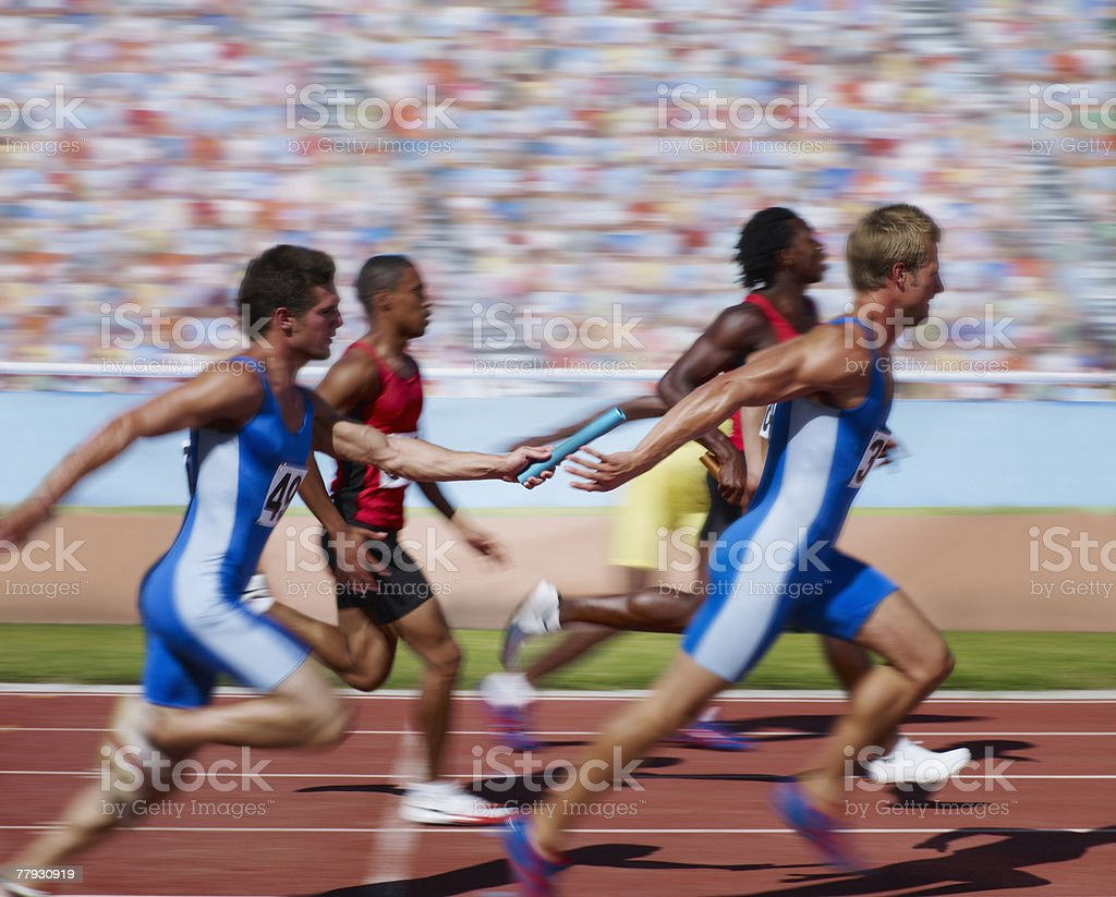 Racers running on track with relay baton stock photo