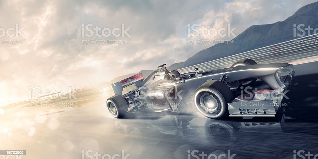 Racing Car Speeding Past on Wet Racetrack At Sunset stock photo