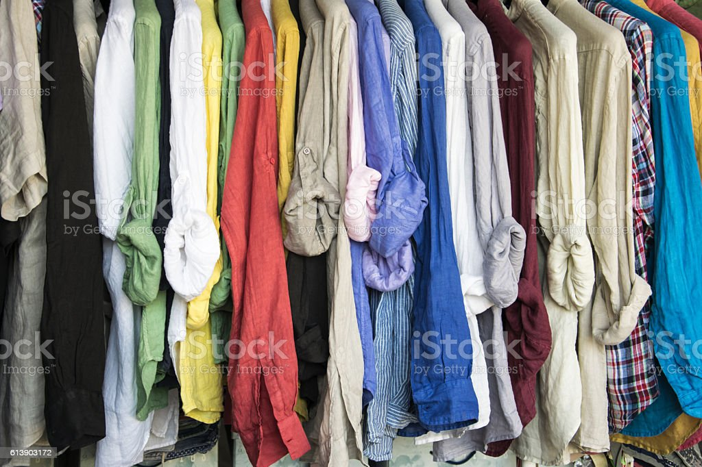 Rack of colorful shirts hanged for sale at the market. stock photo