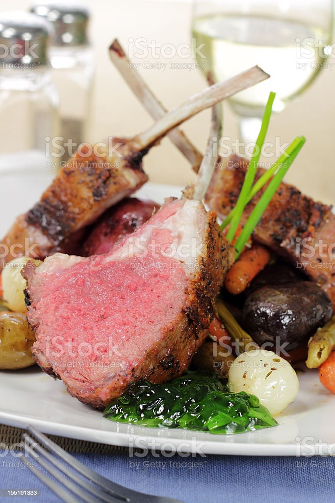 A rack of lamb on a white plate royalty-free stock photo