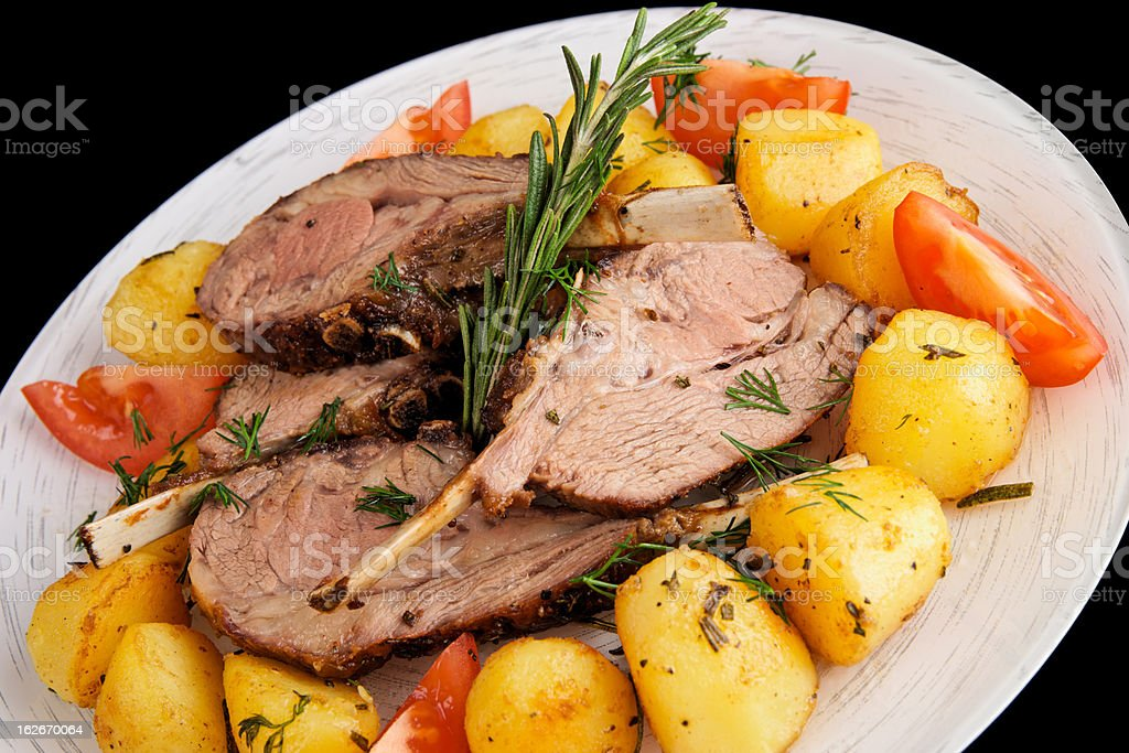 Rack of lamb with fried potatoes isolated on black royalty-free stock photo