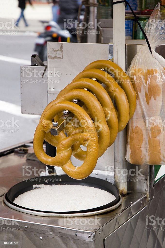 Rack of pretzels hanging over a pan of salt in vendor's cart royalty-free stock photo