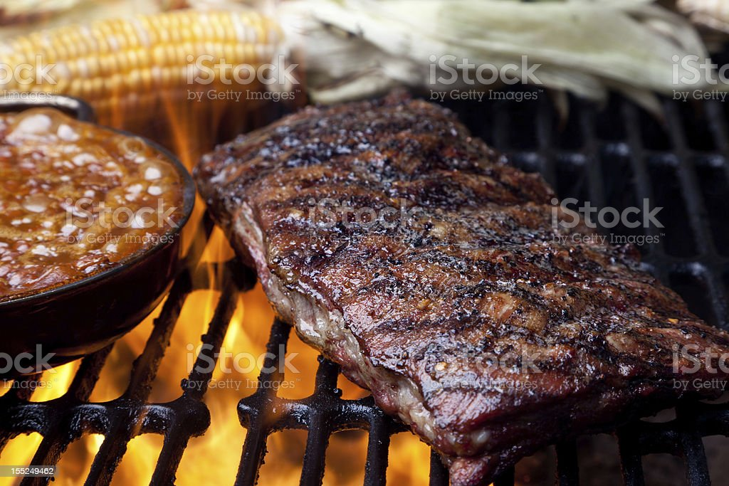 Rack of Ribs and Baked Beans on Flaming Grill royalty-free stock photo