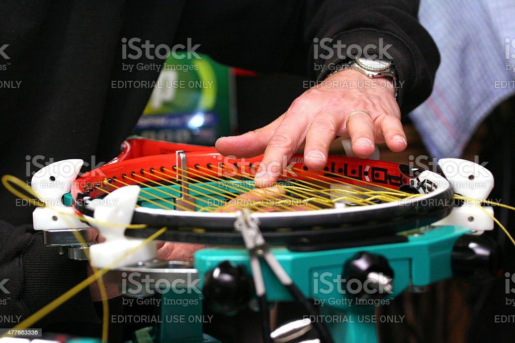 Racquet stringer weaving cross strings on a stringing machine stock photo