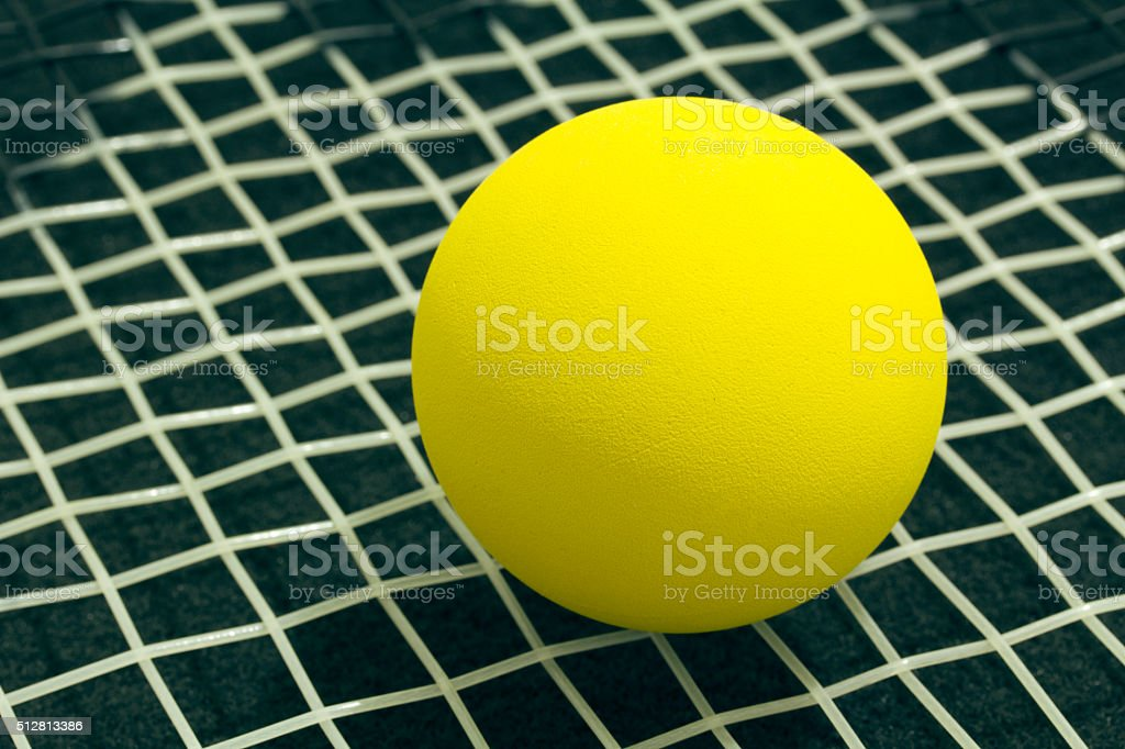 Racquetball on racket strings. Yellow frontenis ball laying on r stock photo