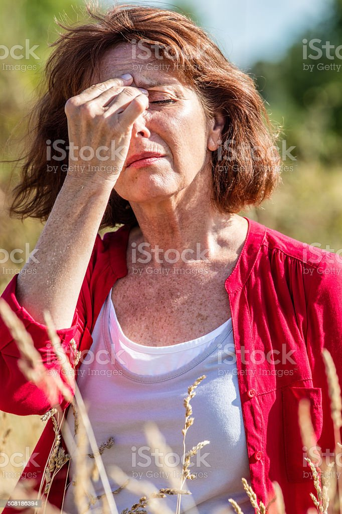 radiant middle aged woman with freckles having sinus pain outdoors stock photo