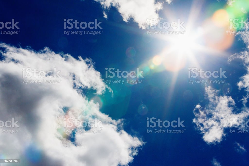 Radiating lens flare from midday sun in lightly clouded sky stock photo