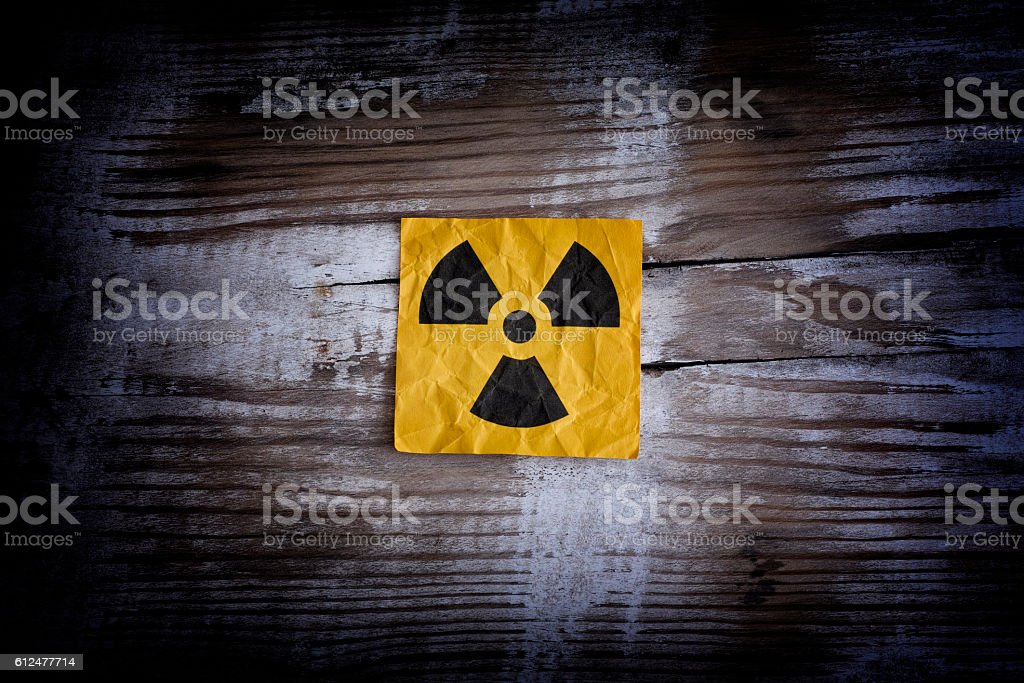 Radiation warning sign on a wooden surface stock photo