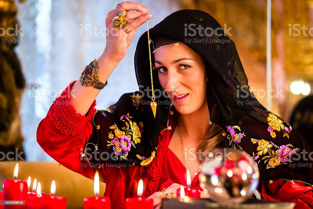 Radiesthesist in Seance dowsing with pendulum stock photo