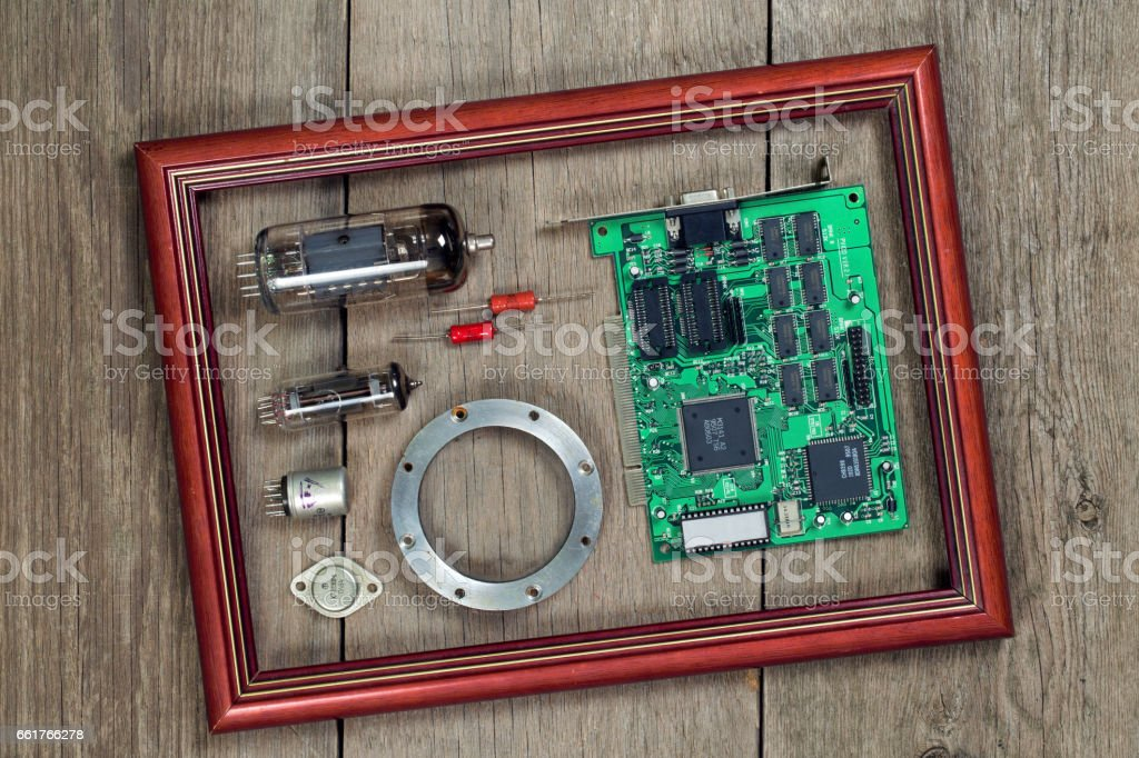 Radio and electronic components in a frame on a wooden table stock photo