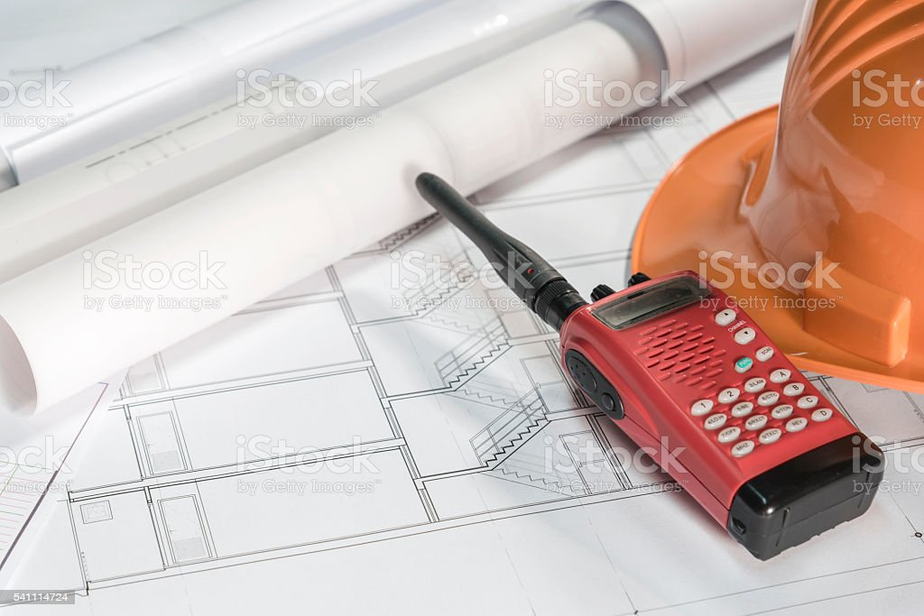 radio communication with helmet over architectural blueprints stock photo