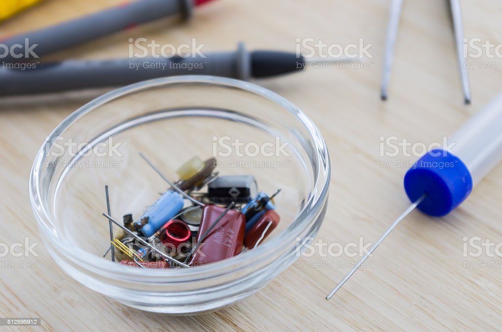 Radio parts in the glassy saucer on the wooden table. stock photo