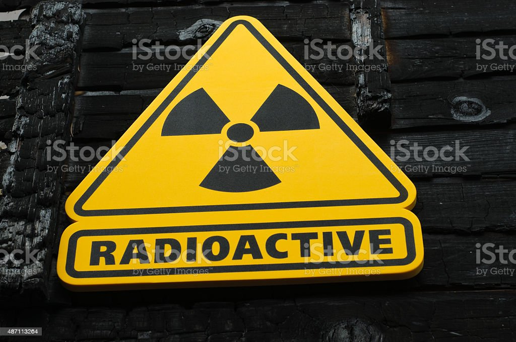 Radioactive Sign on Burned Wooden Background stock photo