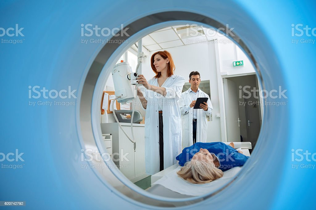 Radiologic technician and Patient being scanned and diagnosed on CT stock photo