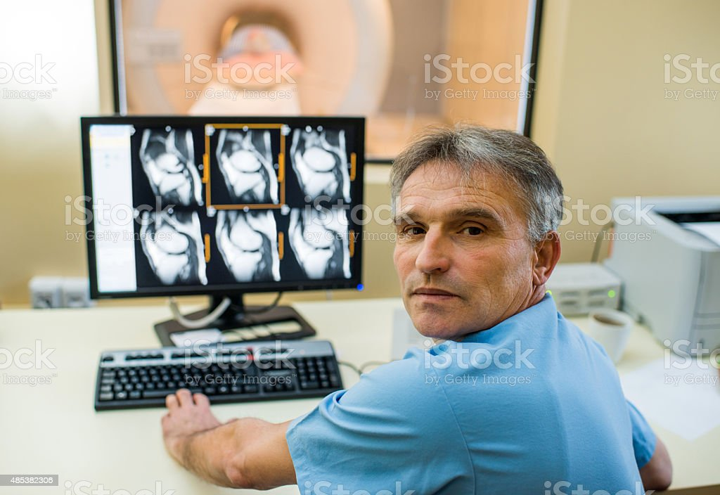 Radiologist analyzing X-ray images and looking at camera. stock photo