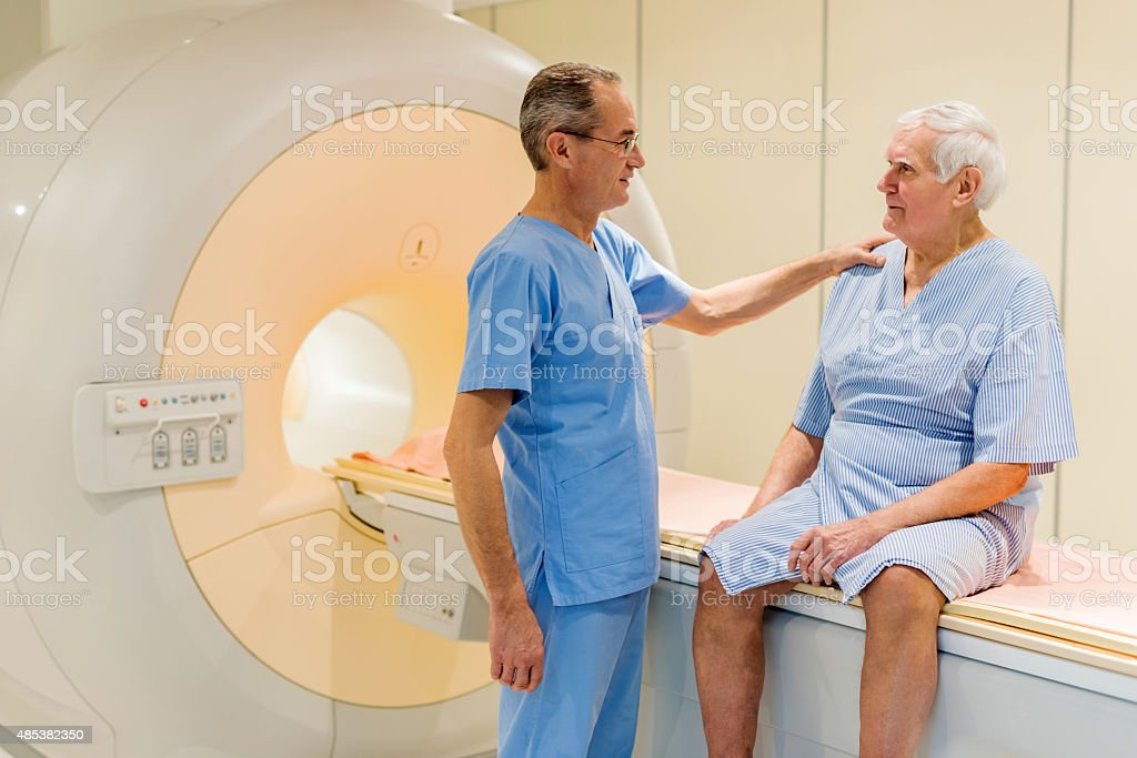 Radiologist communicating with senior patient after MRI scan. stock photo