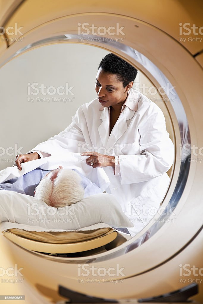 Radiologist preparing patient for PET-CT scanner stock photo