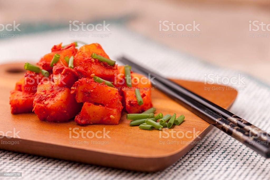 Radish kimchi topped with green onions. stock photo