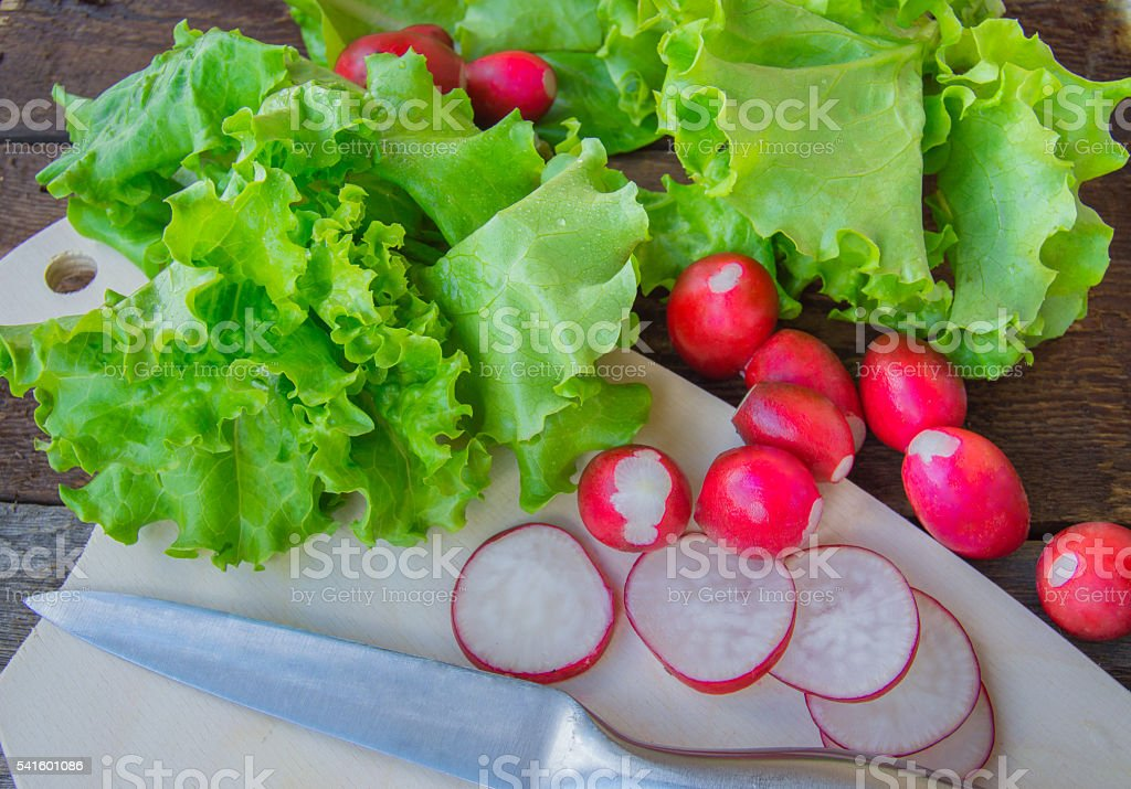 Radishes and fresh organic lettuce on a dark wooden background stock photo