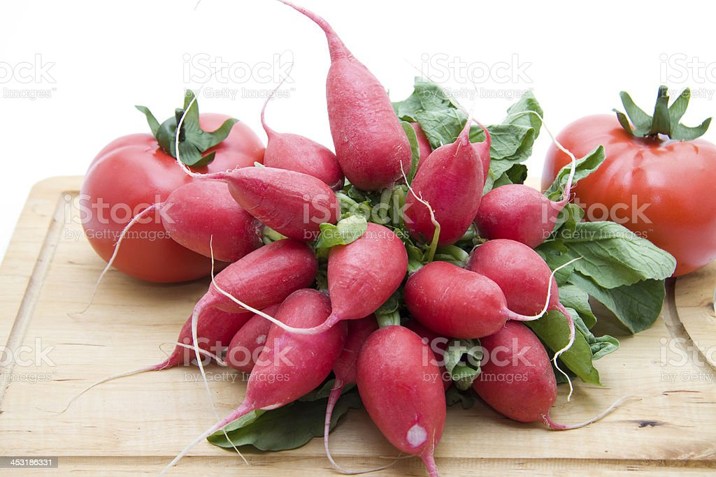 Radishes and tomatoes on edge board stock photo