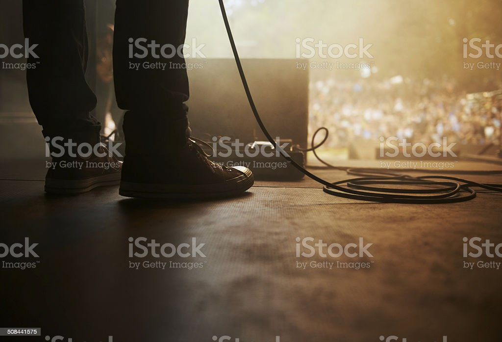 Cropped shot of a musician's feet on stage at an outdoor music...