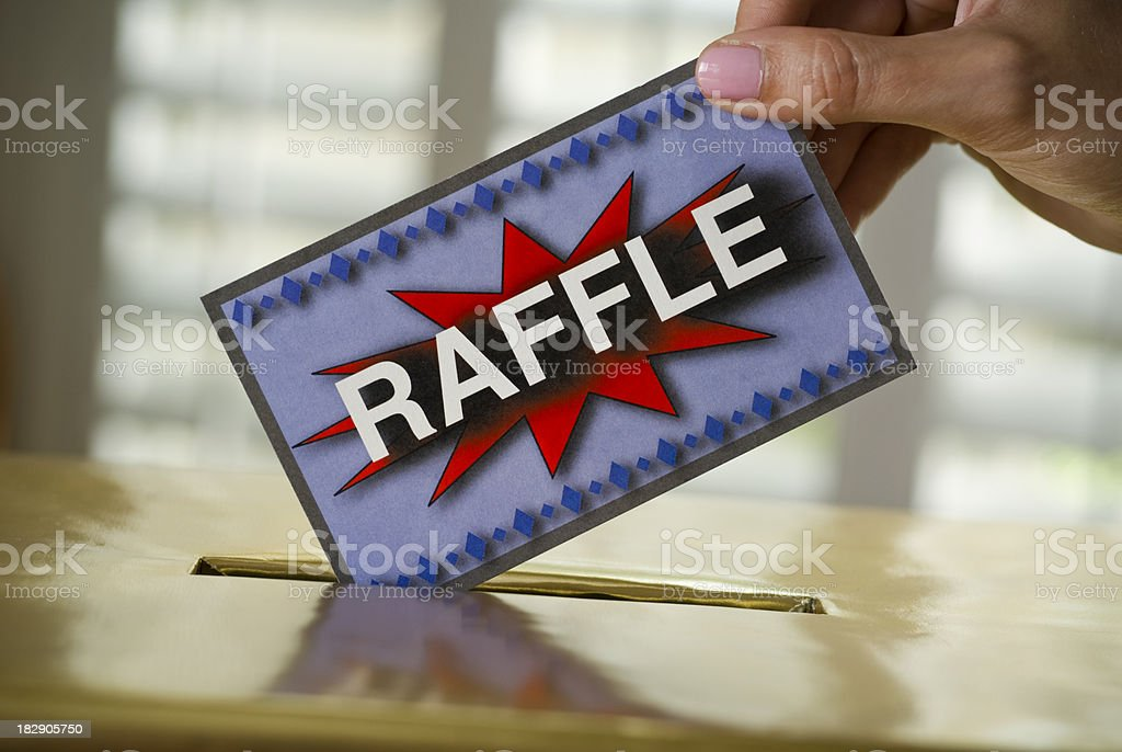 Raffle ticket being dropped into a box stock photo