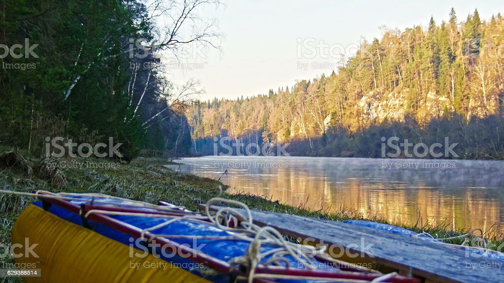 Raft on shore of mountain misty river stock photo