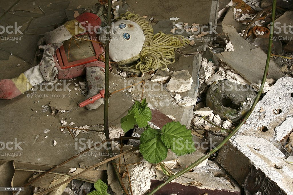 Raggedy Ann Doll in rubble with green leaves stock photo