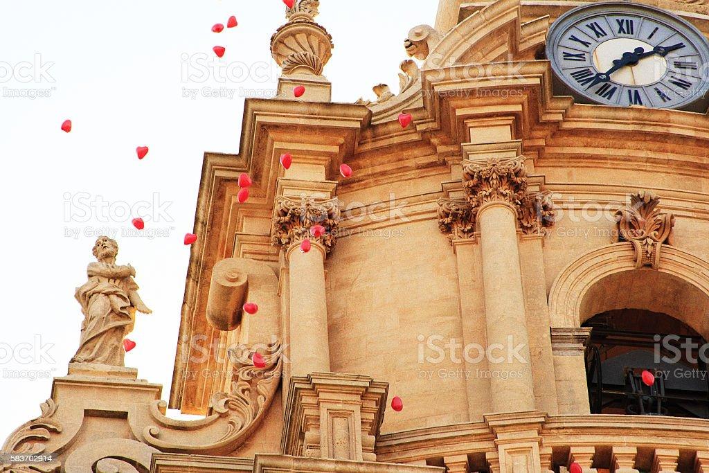 Ragusa Ibla: Red Heart-Shaped Wedding Balloons Rising Near Church stock photo