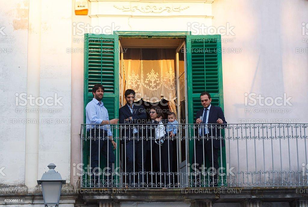 Ragusa Ibla, Sicily: Family on Balcony at Celebration of Saint stock photo