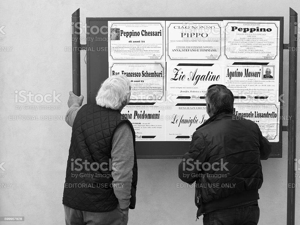 Ragusa Ibla, Sicily: Two Men Reading Public Death Notices, Italy stock photo
