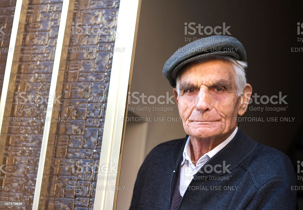Ragusa, Sicily: Senior Man with Traditional Cap Looking Out Window stock photo