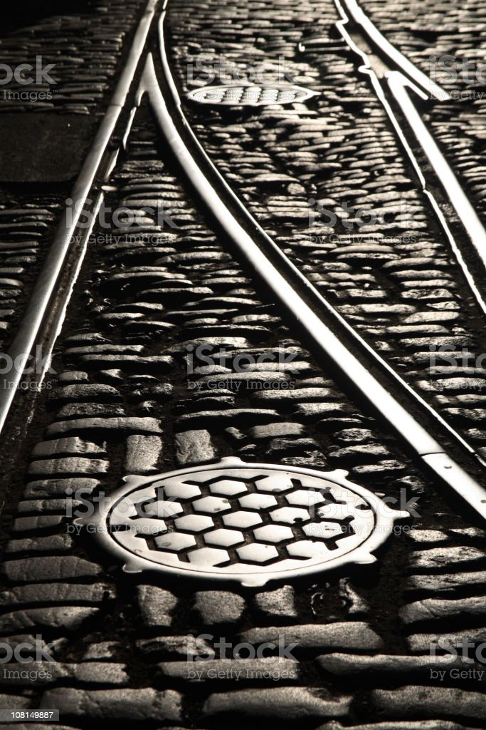 Rail tracks and manholes on cobblestone street 2 royalty-free stock photo