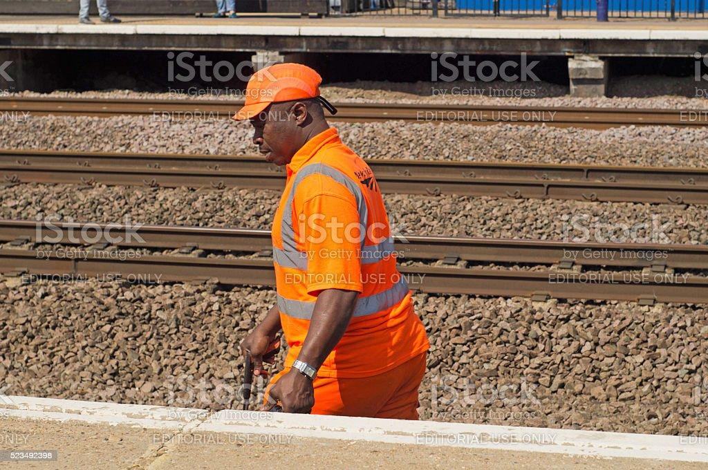 UK Rail worker cleaning tracks of litter stock photo