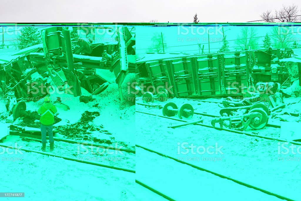 Rail worker inspects damage from coal train crash in snow stock photo