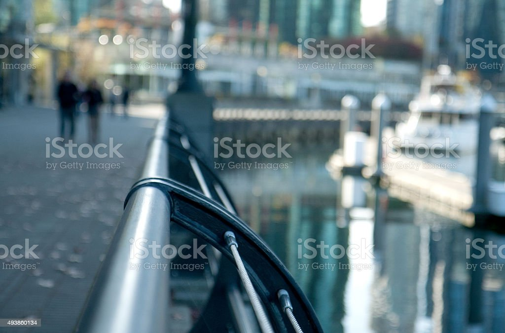 Railing along pathway next to a marina in the city stock photo