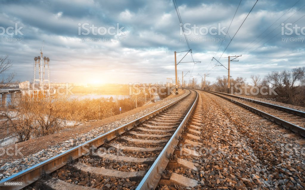 Railroad at sunset. Railway station against blue cloudy sky. Beauty industrial landscape with railroad and bright yellow sunlight. Railway junction in the evening. Heavy industry. Cargo shipping stock photo