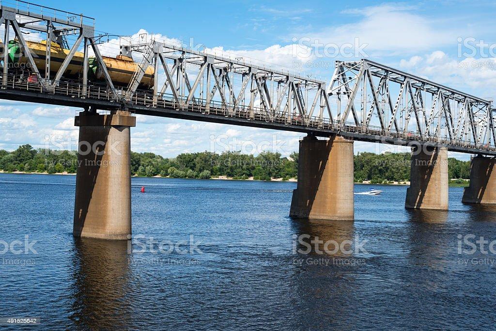 Railroad bridge in Kyiv across the Dnieper with freight train stock photo