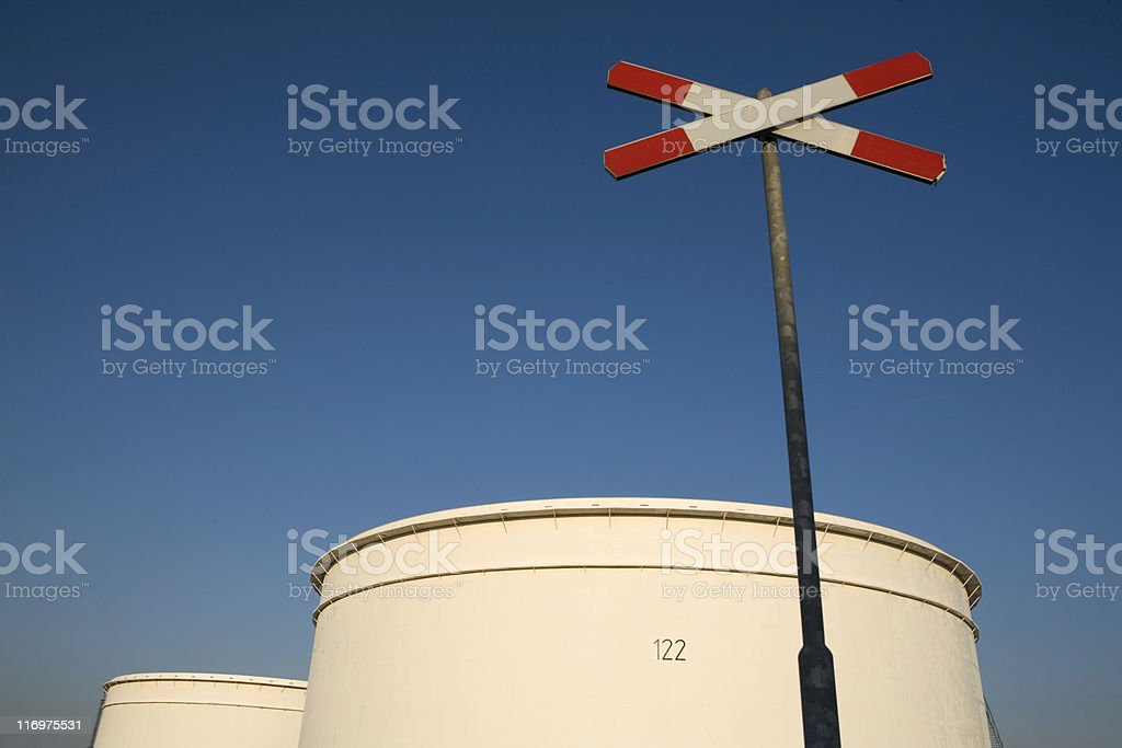 railroad crossing close to storage tanks of an oil refinery royalty-free stock photo