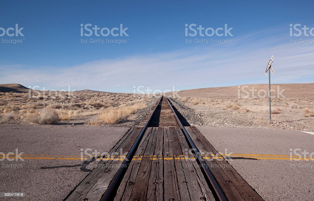 Railroad crossing tracks in the desert stock photo