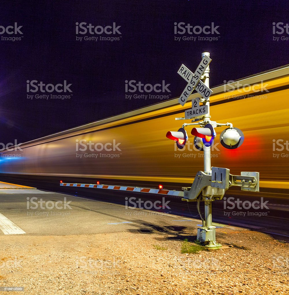 Railroad crossing with passing train by night stock photo
