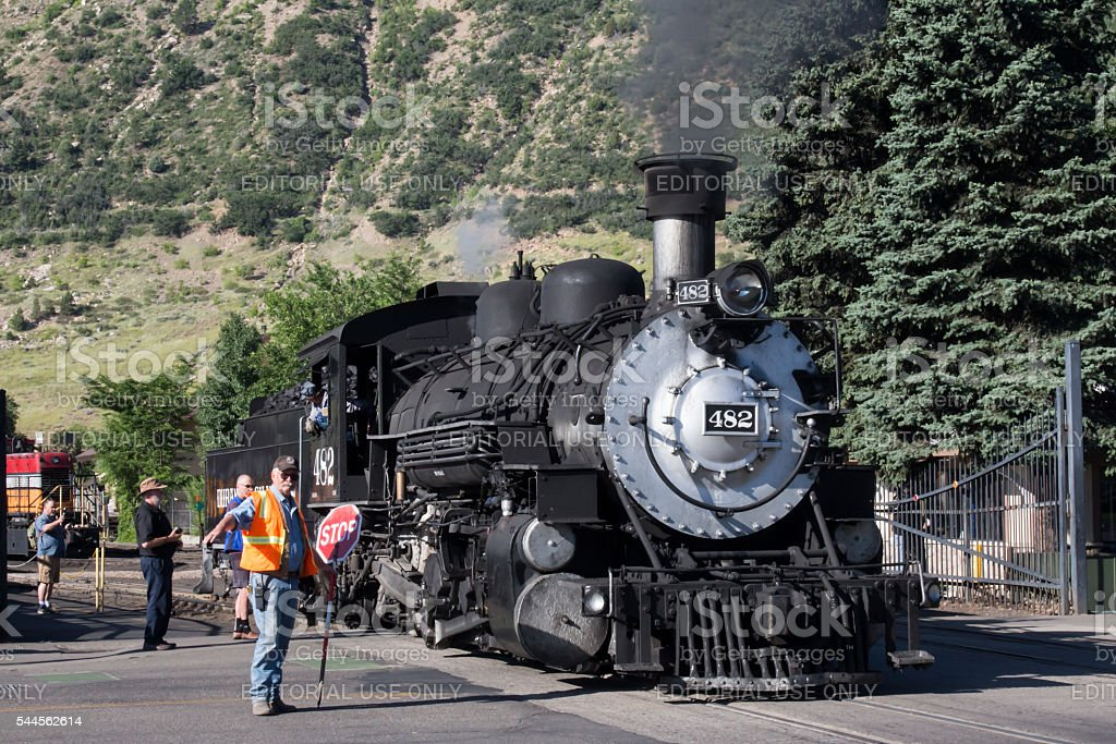 Railroad employee stopping traffic for the steam engine stock photo