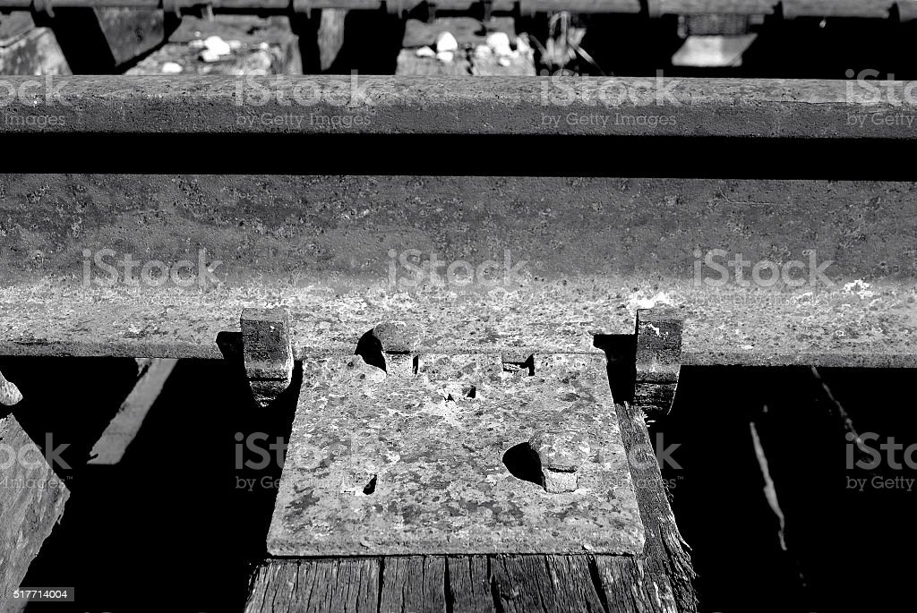 Railroad spikes and clamps holding rail to cross tie stock photo