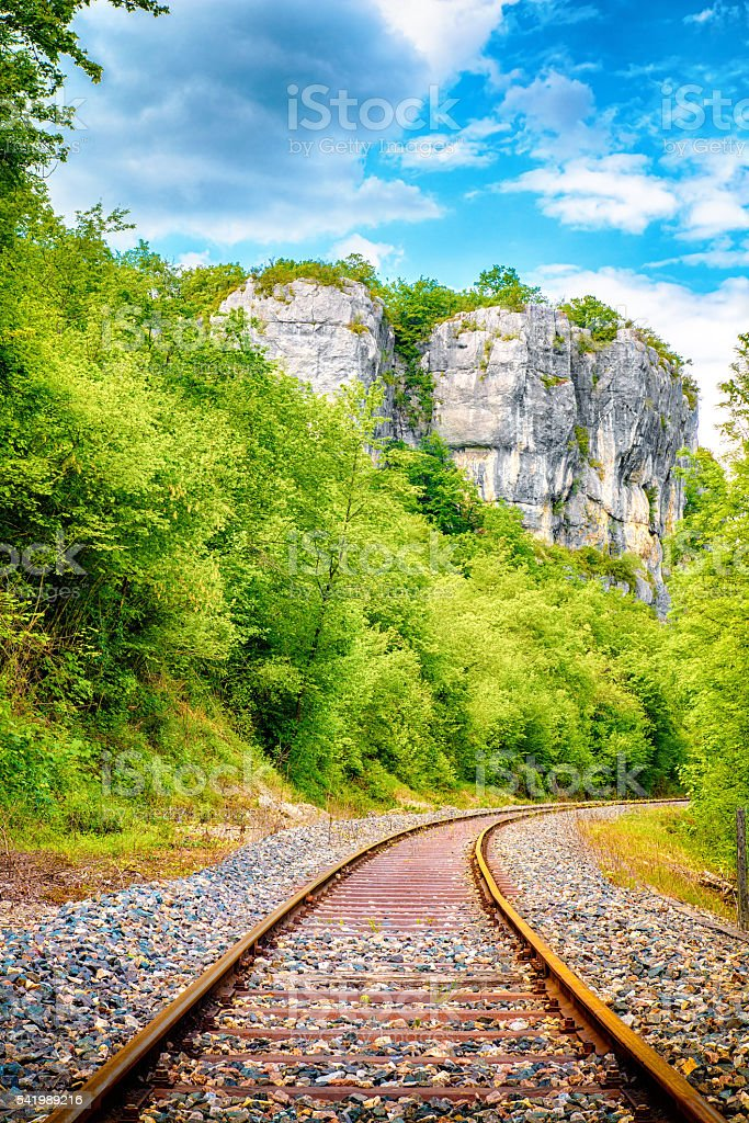 Railroad track diminishing perspective in forest along the cliff stock photo