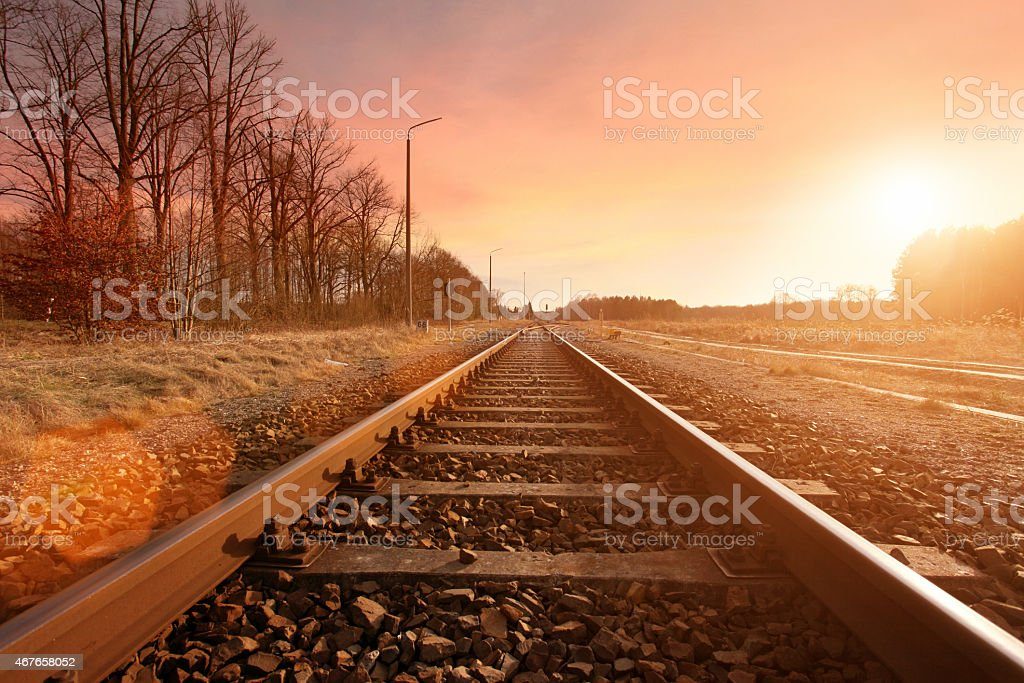 Railroad track running to the horizon in countryside at sunset stock photo