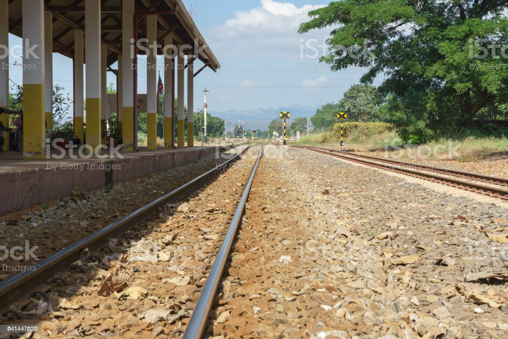 Railroad tracks and platform with mountain and sky background stock photo