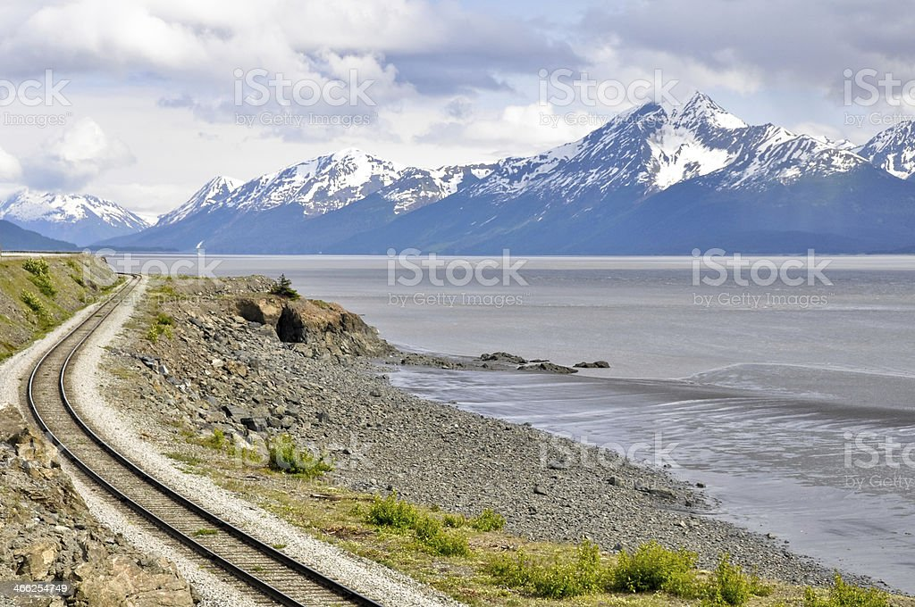 Railroad tracks beside water and mountains in Turnagain Arm stock photo
