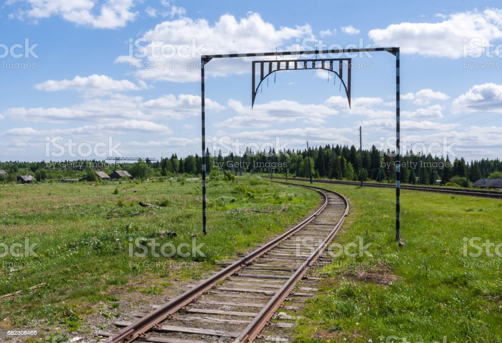 Railroad tracks going into the distance towards the forest and village in summer day. stock photo